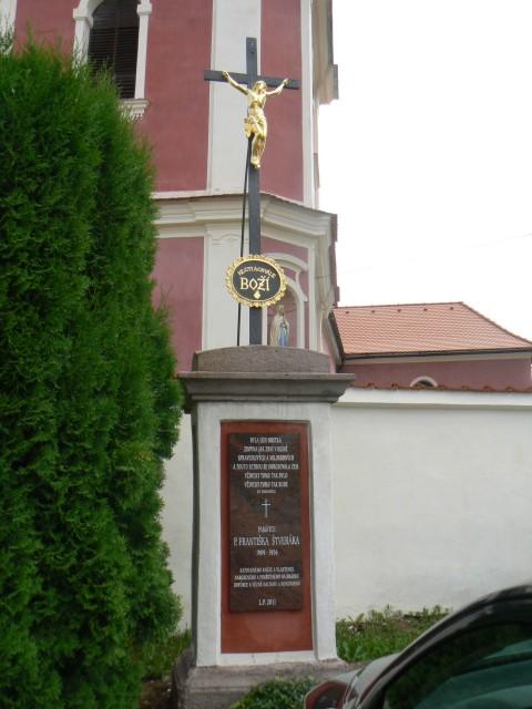 Kříž s pamětní deskou Františka Štveráka před kostelem na Hrádku